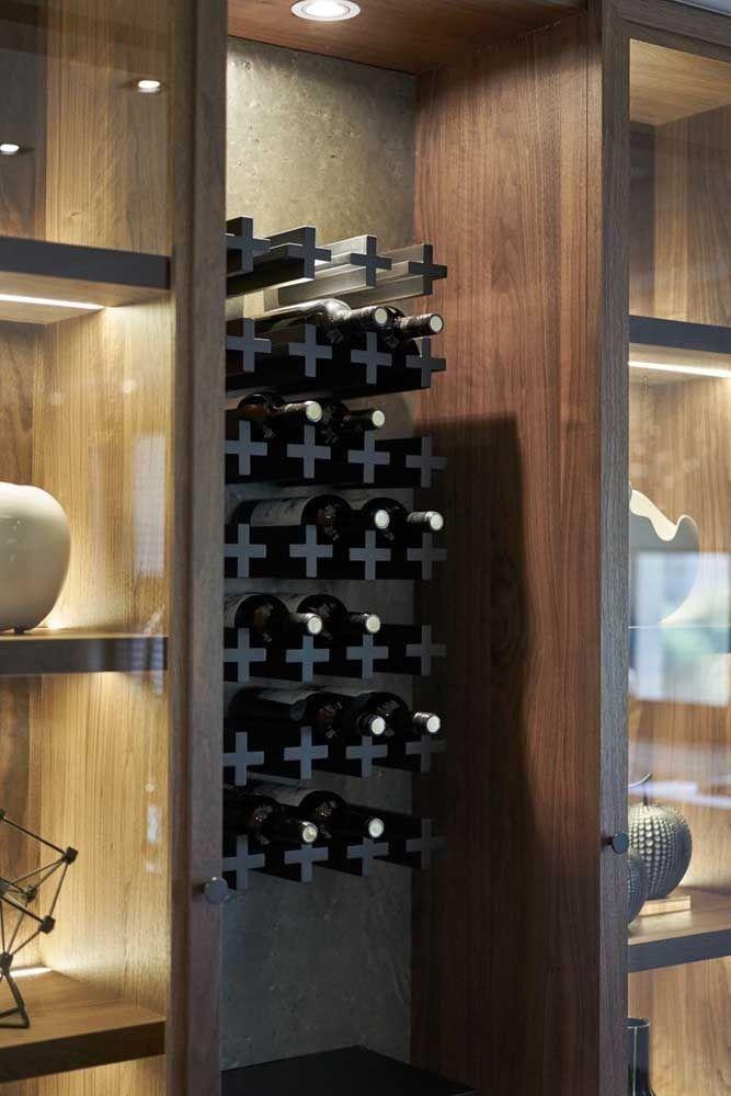 Suporte em formato de cruzes para as garrafas; destaque para a iluminação especial que a adega recebeu