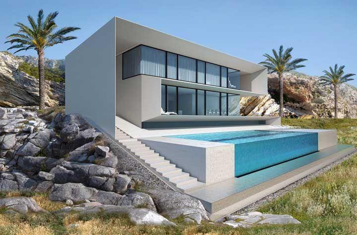A casa contemporânea faz um belo contraste com a paisagem natural, sem contar a piscina de vidro que arrebata o coração de qualquer um