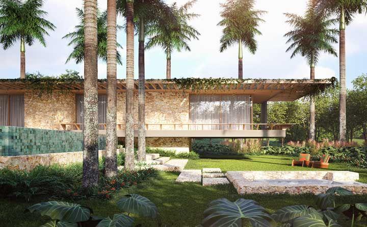 Já essa outra casa de praia apostou em materiais rústicos e naturais para a fachada, como a pedra e a madeira