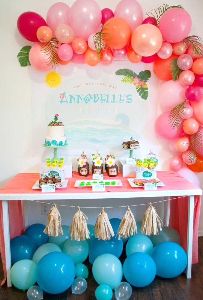 Ao invés de fazer um bolo todo decorado com o tema da Moana, você pode criar um bolo simples e deixar a decoração na mesa