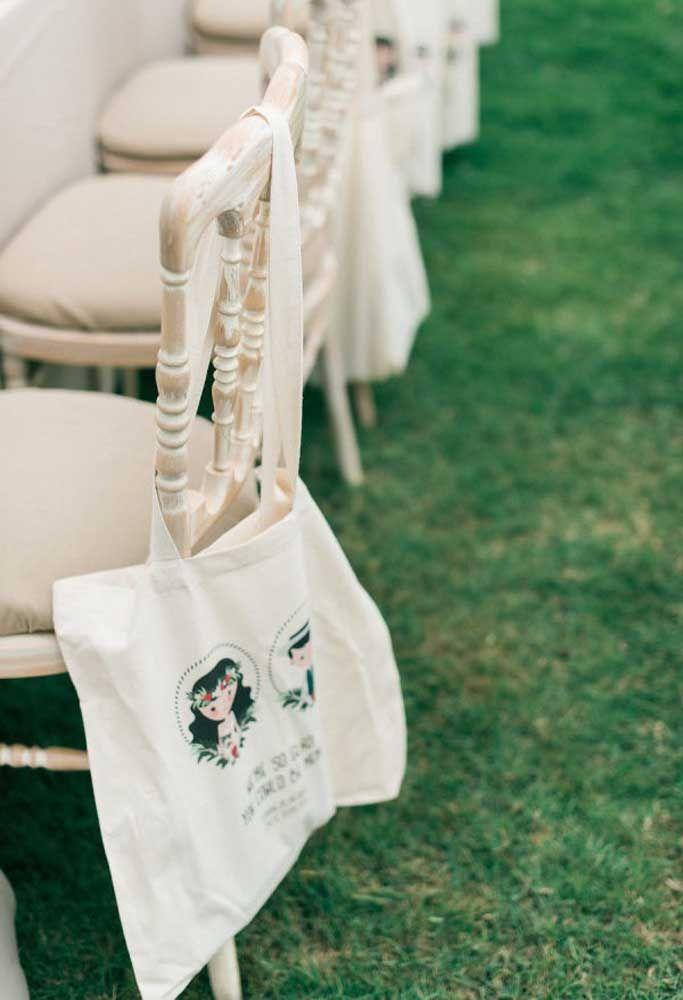 Se você colocar as lembrancinhas de casamento dentro de sacolas grandes, é possível pendurá-las nas cadeiras.