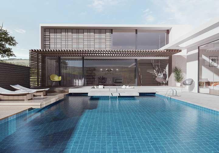 A casa com piscina optou pelo telhado embutido e o uso da platibanda