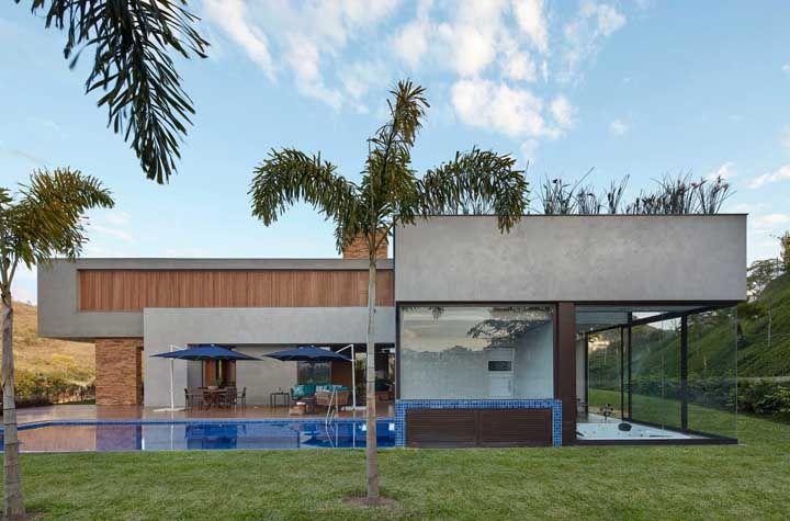 O cimento queimado trouxe um ar rústico e moderno a casa de campo com piscina