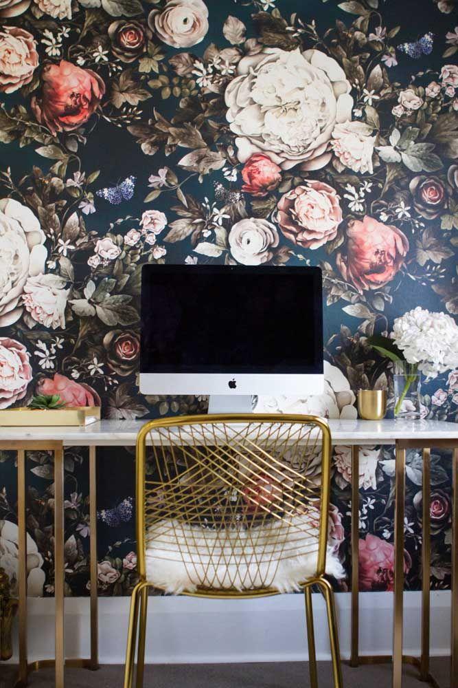 O home office ganhou papel de parede com flores avantajadas e detalhes dourados para garantir um certo glamour