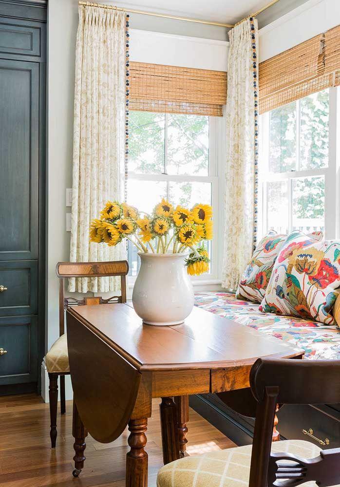 Flores no vaso e nas estampas sobre o sofá
