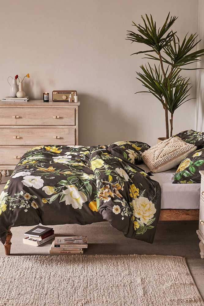 O quarto de casal apostou na estampa floral para a roupa de cama; o fundo preto e as grandes flores amarelas decoram o ambiente sem clichês