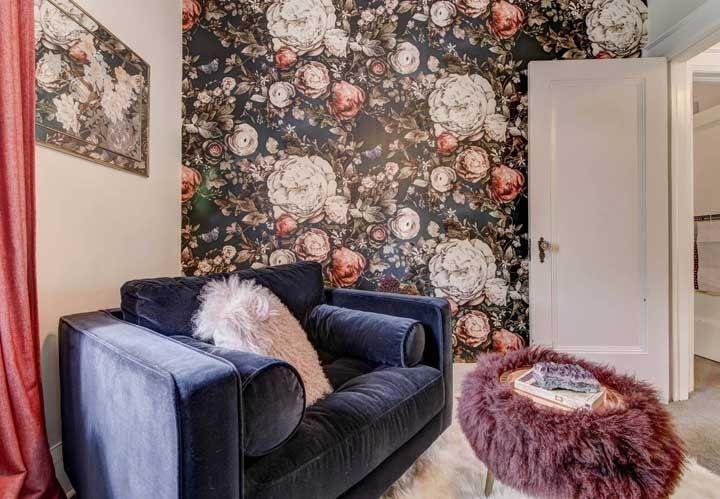 O espelho na parede adjacente dá continuidade ao papel de parede florido