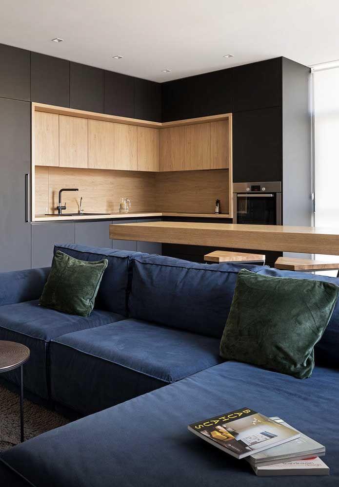 O canto desse sofá em L azul é formado pelo chaise fixo