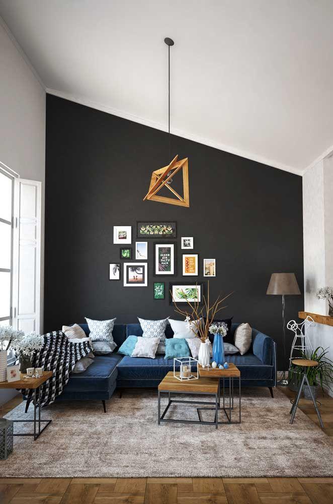 Para contrastar com a parede preta, um sofá de canto azul; arremate a decor com muitas almofadas