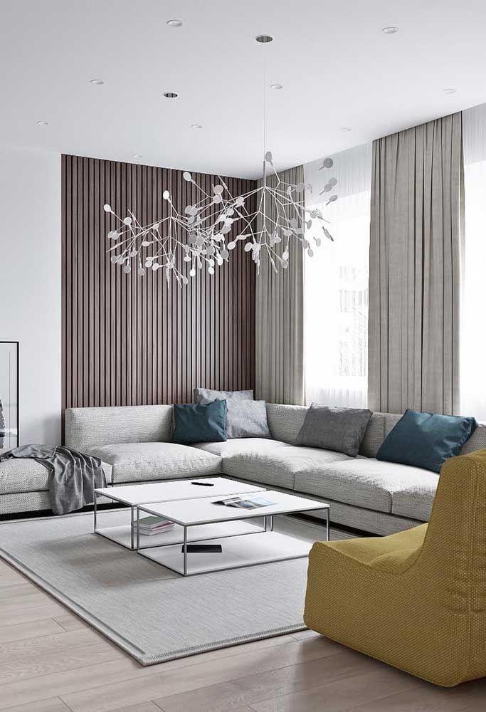 O tom cinza do sofá em L conversa diretamente com a cortina e o tapete da sala