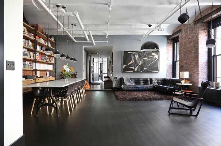 O ambiente amplo e bem iluminado não teve dúvidas em apostar em um sofá preto em L para fechar a decor