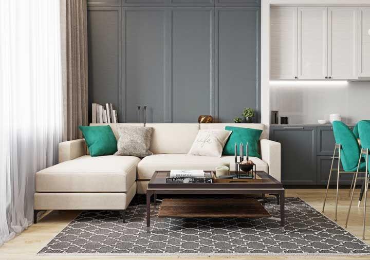 As almofadas sobre o sofá na mesma cor das cadeiras reforçam a ideia de integração dos ambientes