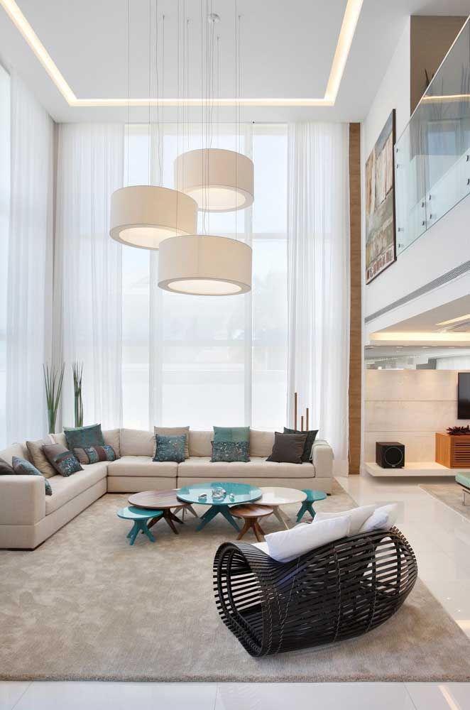 A sala ampla com pé direito duplo apostou no uso de um sofá de canto em tom de Off White; pura elegância e neutralidade