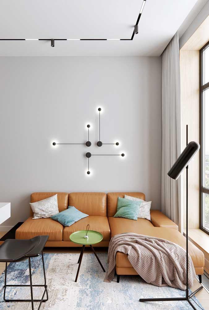 O couro de cor caramelo do sofá deixa o ambiente sofisticado, enquanto o formato com chaise fixo traz modernidade para a sala