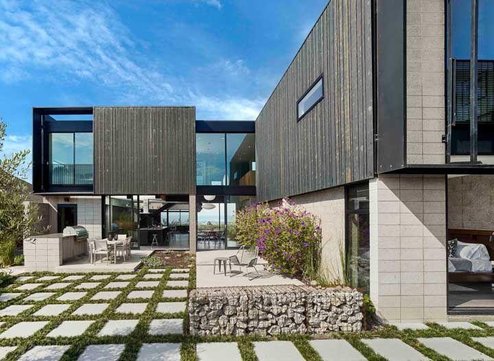 A fachada mais rústica apostou no uso do concregrama combinado a gambiões de pedra