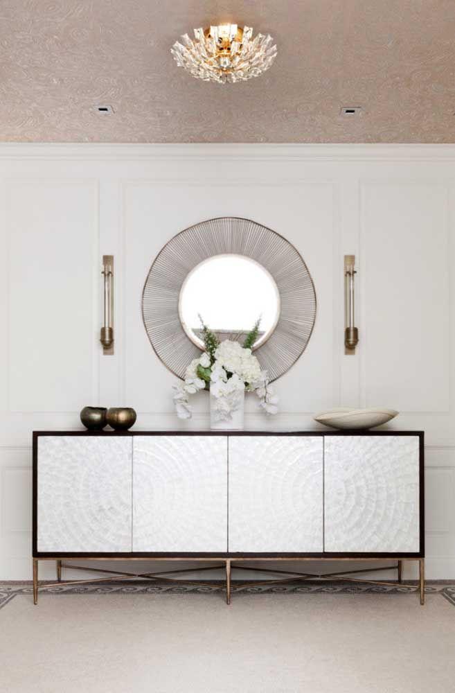 Nessa proposta elegante de decoração, o espelho redondo com moldura diferenciada foi complementado com a presença das luminárias de parede