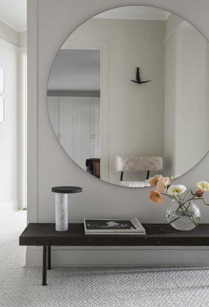 Já nesse outro hall, a opção foi usar um espelho redondo cobrindo quase toda a parede combinado a um banquinho baixo que também serve de apoio para objetos decorativos