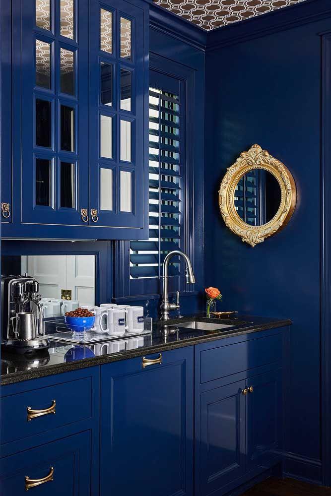Uma cozinha digna de realeza: para conseguir esse efeito bastou combinar a elegância do azul com o glamour dourado do pequeno espelho redondo