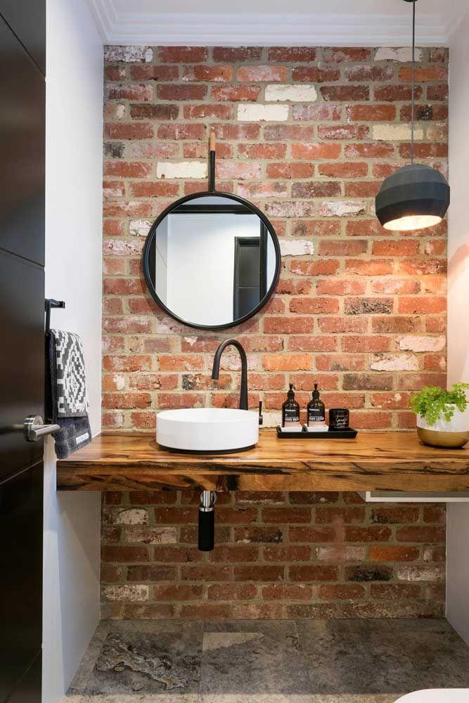 O espelho redondo caiu como uma luva nesse banheiro de estilo rústico industrial