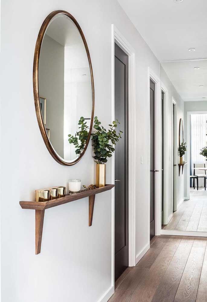 O espelho redondo desse hall decora o ambiente com a moldura dourada; o trabalho de ampliar o ambiente fica por conta do espelho que cobre a parede adjacente