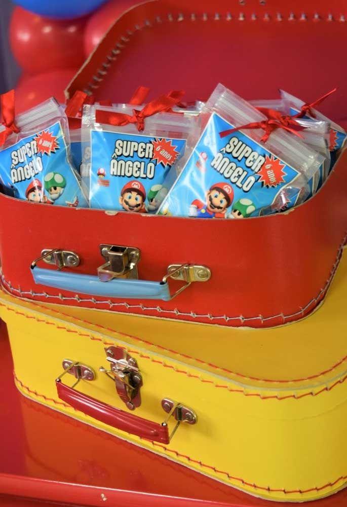 Para colocar as lembrancinhas, separe algumas malas nas cores do tema. Além de ficar mais organizado, o item combina perfeitamente com a decoração.