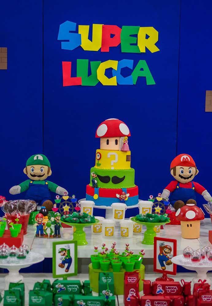 Uma mesa repleta de personagens e elementos que fazem referência ao Super Mario Bros, além de muitas guloseimas.