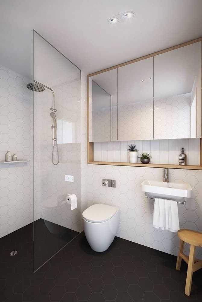 Nesse banheiro, a moldura de madeira do espelho se revela um nicho na parte inferior