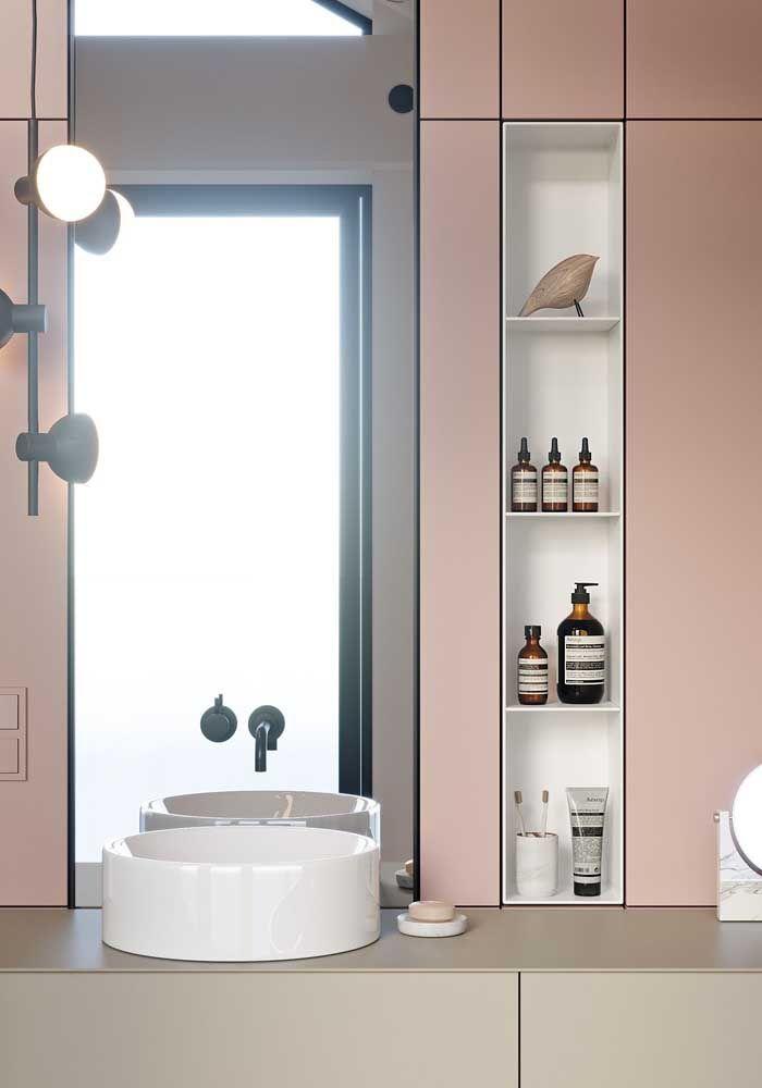 O banheiro rosa conta com um nicho vertical embutido no próprio armário