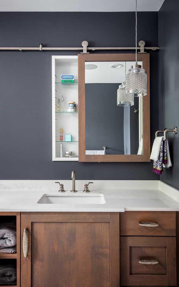 Nada mais moderno e sofisticado do que uma parede azul petróleo com móveis de madeira escura, os nichos arrebatam a decor exibindo discretos utensílios do cotidiano