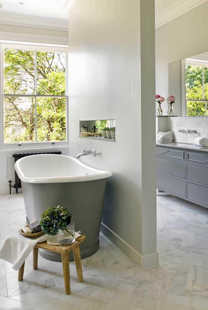 A parede que divide os dois ambientes traz um nicho vazado que, discretamente, acaba por integrar novamente o banheiro