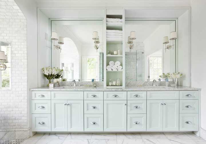 O banheiro de decoração clássica apostou em uma fileira de nichos verticais para separar as duas partes da bancada