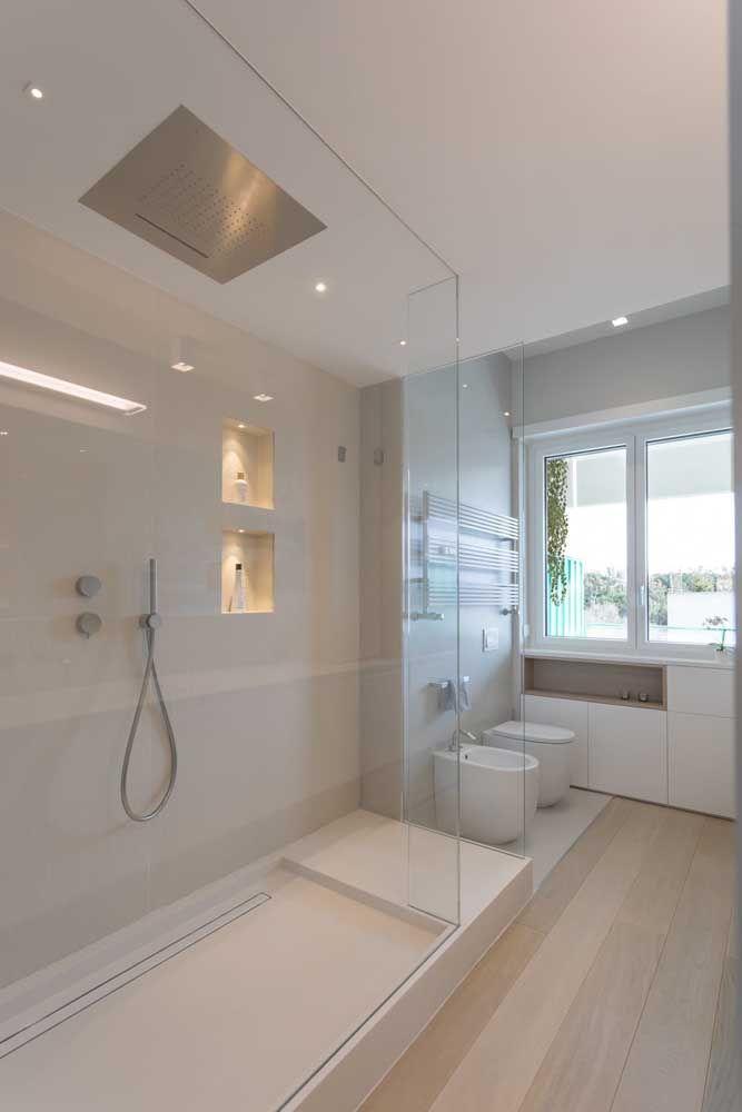 O banheiro branco, moderno e minimalista traz dois nichos embutidos na parede que passam de modo suave e discreto pelo olhar