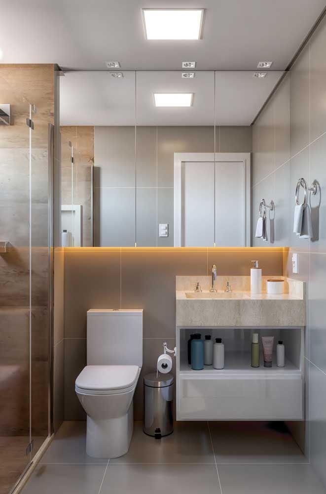 A bancada de granito desse banheiro pequeno foi usada para criar um nicho que serve para acomodar itens de higiene pessoal
