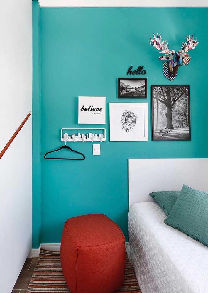 A proposta aqui foi marcar a parede com uma cor vibrante e colocar sobre ela quadros de tamanhos variados em preto e branco