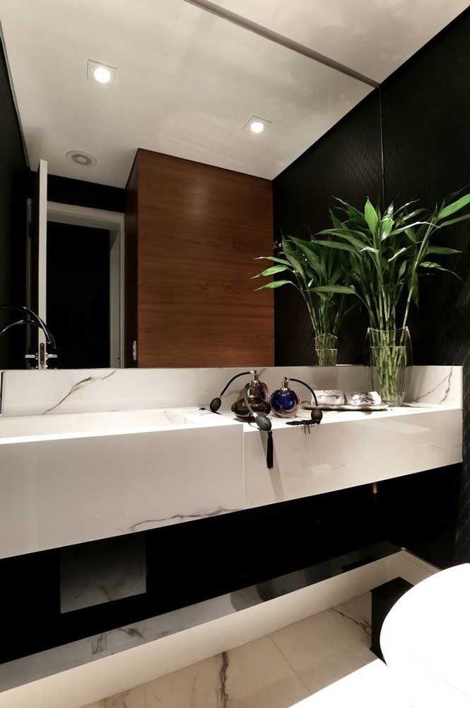 O verde do bambu da sorte cria contraste e garante vida ao banheiro preto e branco