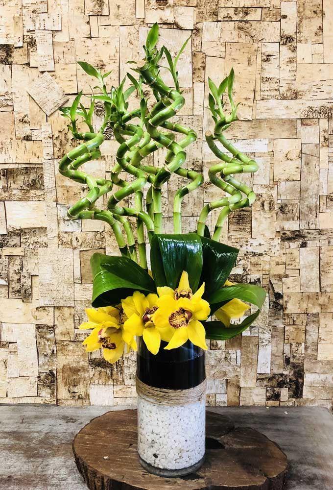 As flores incrementam o arranjo de bambu da sorte e trazem um toque extra de sofisticação a planta