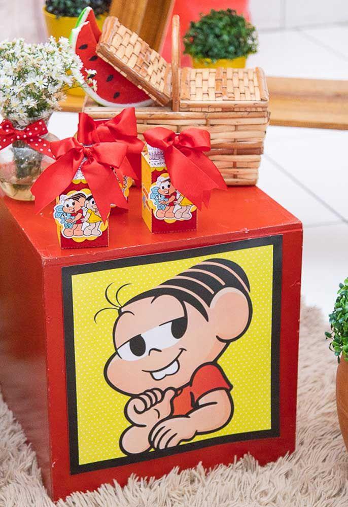 Você pode colocar alguns elementos decorativos da festa em cima de caixotes personalizados com os personagens da Turma da Mônica.