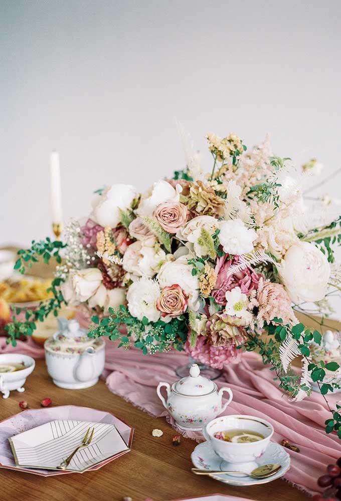 O arranjo de flores no centro da mesa é o destaque desse chá da tarde, mas as louças delicadas de porcelana não passam despercebidas