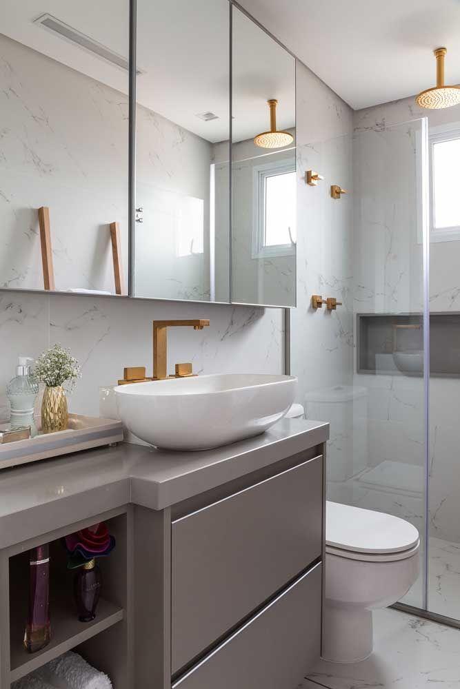 Quer esbanjar charme e elegância no banheiro? Então escolha o granito cinza absoluto para a bancada da pia; complete a proposta com metais dourados