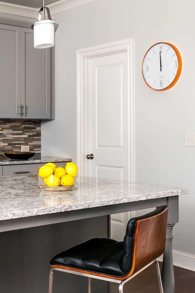 A neutralidade dessa cozinha com granito cinza foi amenizada com o uso de pequenos objetos de cor viva e vibrante