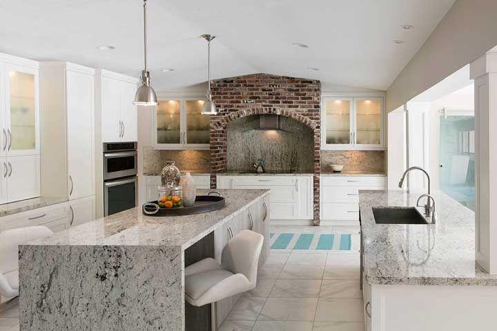 Os tijolos de demolição quebram a predominância do cinza que vem tanto na bancada de granito, quanto no chão de porcelanato