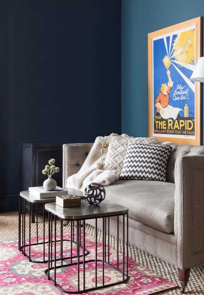 Alguns livros, almofadas e um quadro alegre e cheio de vida formam a decoração com enfeites dessa sala
