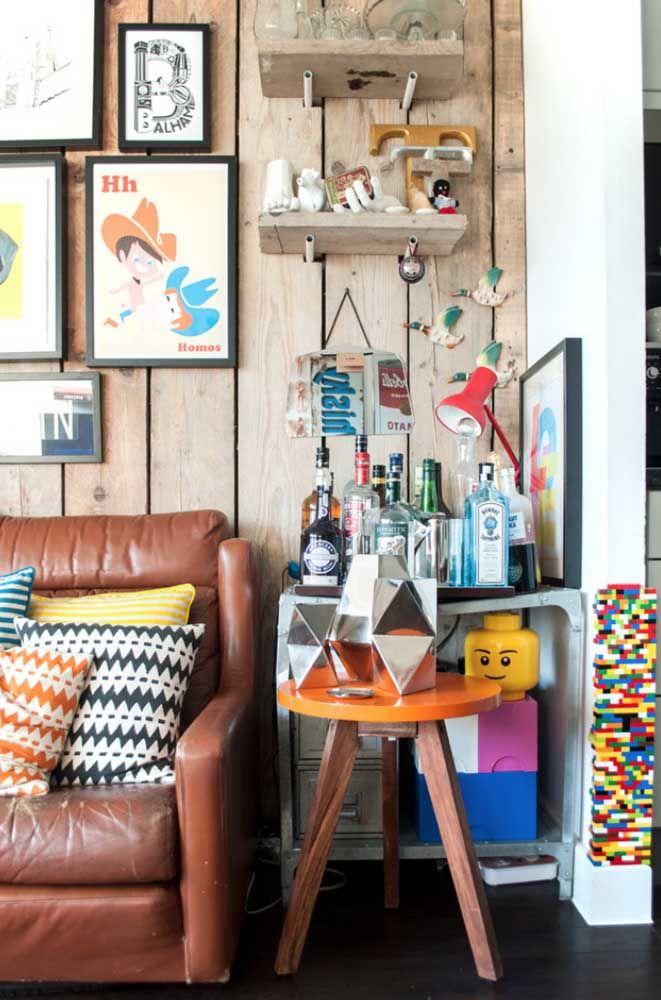 Crie um cantinho cheio de personalidade na sala; aqui, o espaço foi aproveitado para um mini bar, quadros e prateleiras
