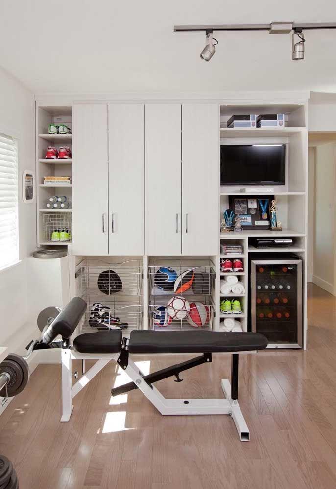 Academia em casa com armário planejado: direito até a TV e mini geladeira