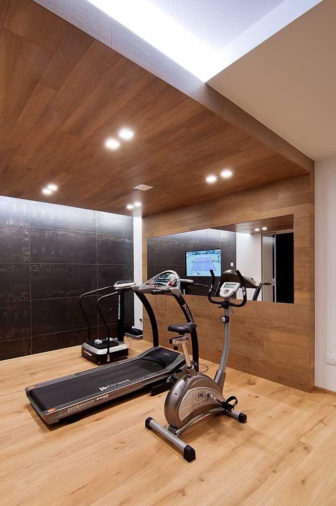 A madeira traz conforto extra para essa academia doméstica; repare na faixa de espelho na parede, na medida ideal para o treino