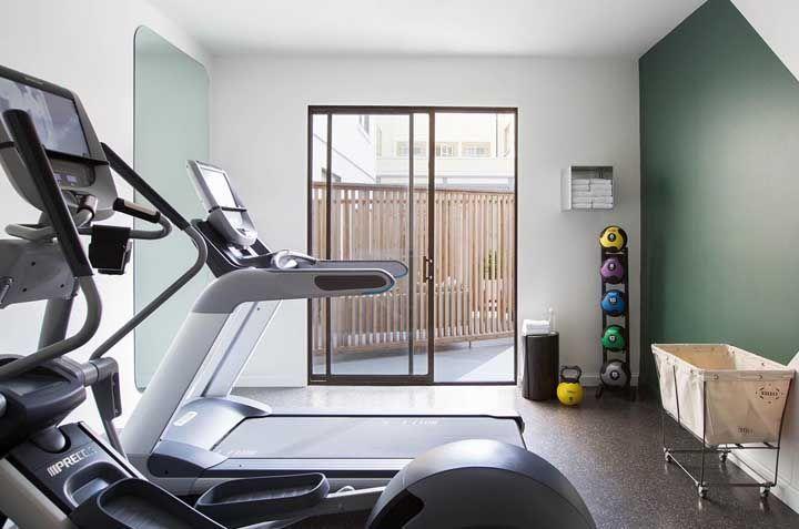 De um lado, o espelho para auxiliar o treino e do outro, uma parede geométrica para deixar a academia em casa mais bonita