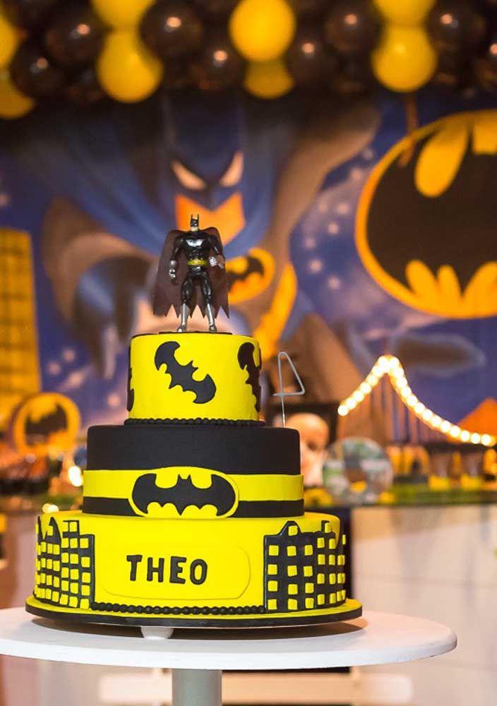 O bolo amarelo e preto para combinar com o restante da decoração. No topo, coloque o boneco do Batman.