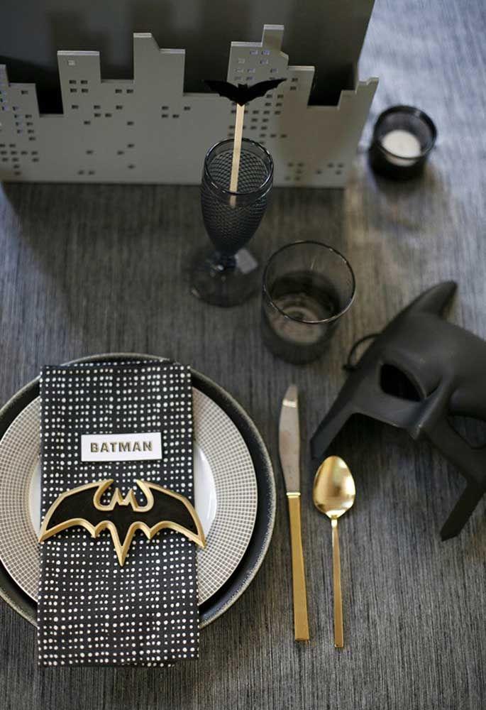 Capriche na decoração da mesa. Use pratos com estampas que fazem referência ao tema, personalizer o guardanapo e use o símbolo do Batman. Para ficar ainda mais personalizado, coloque uma máscara do Homem Morcego como objeto de decoração.