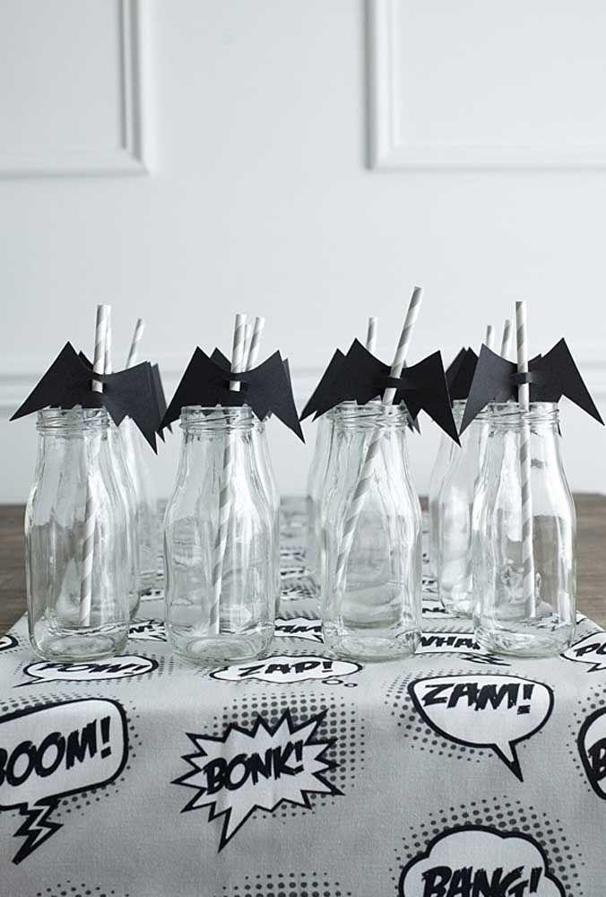 Ao invés de usar copos, use algumas garrafas transparentes para servir a bebida. Para personalizar, coloque a figura do morcego nos canudos.