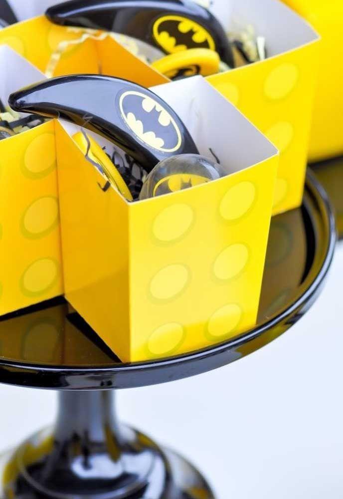 Você pode usar caixinhas de papel personalizada com o tema Batman para colocar guloseimas e entregar como lembrancinha da festa.
